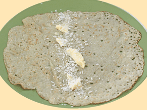 dessicated coconut and butter spread on  Appau/pancake, ready to be rolled and eaten