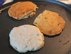 Crumpets cooking in non-stick pan with minimal oil